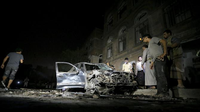 People check a car damaged by a car bomb attack near a mosque in Yemen's capital Sanaa