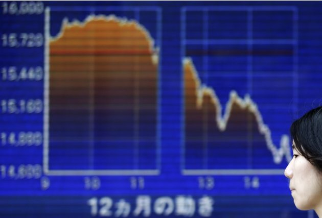 A woman walks past an electronic board displaying a graph showing a dramatic turnaround of Japan's Nikkei average outside a brokerage in Tokyo