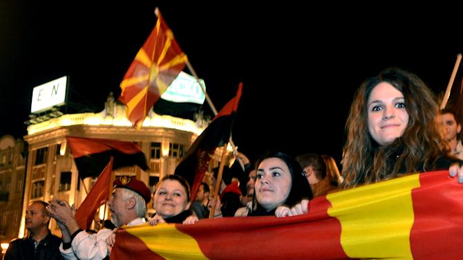 Supporters of Macedonian Prime Minister Nikola Gruevski's party wave party and national flags while celebrating the party's victory in local elections, in downtown Skopje, Macedonia, early Monday, March 25, 2013.  Macedonians voted peacefully in local elections Sunday, boosting hopes the country is turning a page and won't repeat the political and ethnic violence that has marred past voting cycles. (AP Photo/Boris Grdanoski)