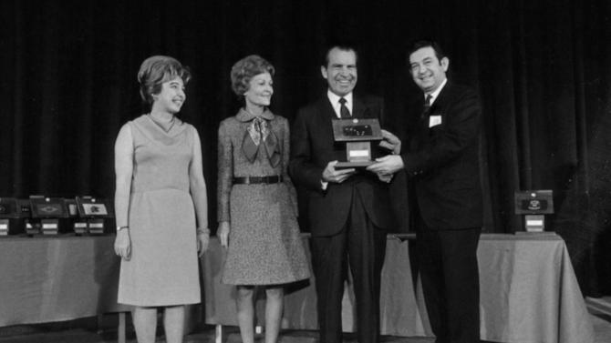 In this Dec. 3, 1969 photo provided by of the Richard Nixon Presidential Library, President Richard Nixon presents Moon rocks to then Governor of Alaska Keith Mille, right, as Pat Nixon, second left, and Diana Miller look on at the Governors Conference in Washington. Alaska officials are contesting a lawsuit filed by a former resident who claims he rescued the moon rocks from a garbage heap 38 years ago. (AP Photo/Richard Nixon Presidential Library, Robert L. Knudsen)