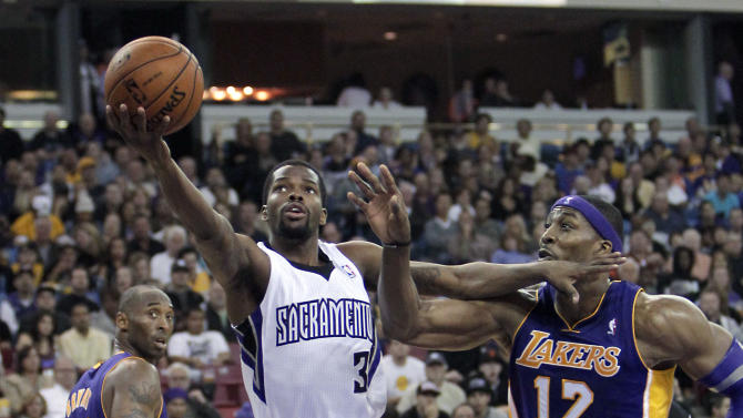 Sacramento Kings guard Aaron Brooks, center, drives to the basket against Los Angeles Lakers center Dwight Howard, right, as Kobe Bryant, left, watches during the second half of an NBA basketball game in Sacramento, Calif., Wednesday, Nov. 21, 2012. The Kings won 113-97. (AP Photo/Rich Pedroncelli)