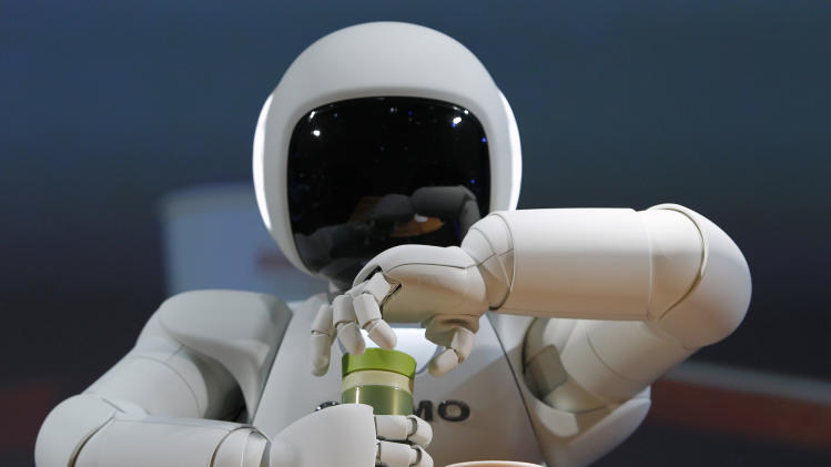 Honda Motor Co's Asimo humanoid robot opens the top of a bottle at the 42nd Tokyo Motor Show