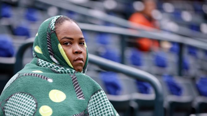 Isha Price, Venus Williams' sister, braves the cold and off-and-on rain during Williams' match against Varvara Lepchenko at the Family Circle Cup tennis tournament in Charleston, S.C., Friday, April 5, 2013.  (AP Photo/Mic Smith)