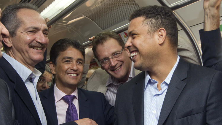 Brazil's former soccer players and members of the local organizing committee for the 2014 World Cup, Ronaldo, right, and Bebeto, second from left, Brazil's Sports Minister Aldo Rebelo, left, and FIFA Secretary General Jerome Valcke, ride a commuter train on their way to visit to the Corinthians' stadium, which is under construction and will host the opening match of the World Cup in 2014, in Sao Paulo, Brazil, Wednesday, Nov. 28, 2012. Officials are revising the construction work being done at stadiums ahead of the Confederations Cup soccer tournament in 2013 and the 2014 FIFA World Cup soccer tournament. (AP Photo/Andre Penner)