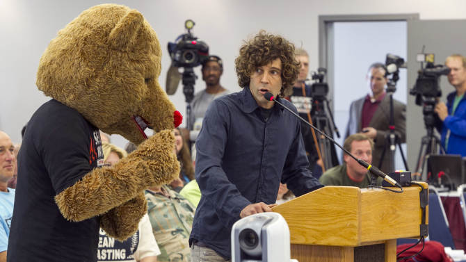 """Environmentalist Jim Brown, right, uses a bear's inability to speak to exemplify """"animals rights,"""" as he addresses the California Coastal Commission meeting in Santa Monica, Calif. Wednesday, Nov. 14, 2012. The California Coastal Commission is weighing whether to grant a permit to the Pacific Gas & Electric Co. to conduct seismic imaging off the coast of the Diablo Canyon nuclear plant. (AP Photo/Damian Dovarganes)"""