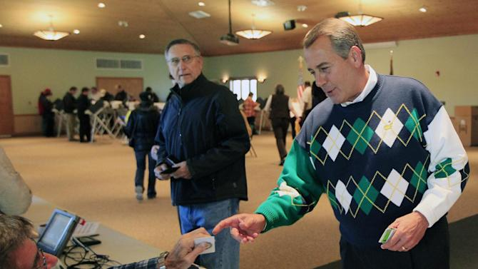 Speaker John Boehner, R-Ohio, presents a photo id as he gets his ballot to vote, Tuesday, Nov. 6, 2012, at Ronald Reagan Lodge in West Chester, Ohio.   After a grinding presidential campaign, Americans head into polling places across the country. (AP Photo/Al Behrman)