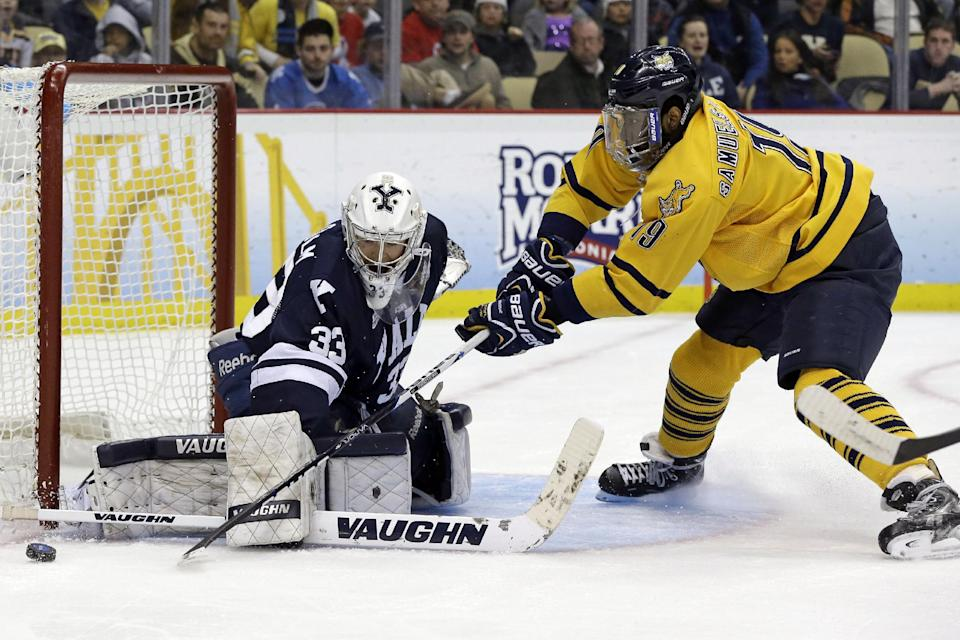 Quinnipiac's Jordan Samuels-Thomas (19)  has a shot blocked by Yale goalie Jeff Malcolm (33) during the first period of the NCAA Frozen Four men's college hockey national championship game in Pittsburgh on Saturday, April 13, 2013. (AP Photo/Gene Puskar)