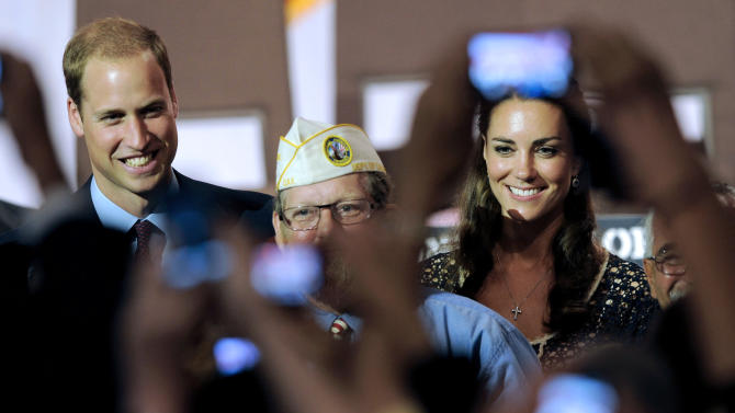 FILE - In this July 10, 2011, file photo, Prince William and wife Kate, the Duke and Duchess of Cambridge, are photographed by fans during a visit to the U.S. in Culver City, Calif. The palace announced Monday, Dec. 3, 2012, that Prince William and wife Kate are expecting their first child_ and it seems at times that Americans may be more enthralled by the news than the Brits. There are several reasons for the American public's pleasure in Kate's news, manifested not only by the good wishes sent by President Obama but also by the breathless news coverage and the general good will toward the couple. (AP Photo/Chris Pizzello, File)