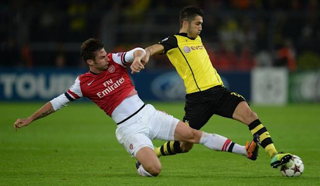 Mikel Arteta (left) challenges Dortmund's Nuri Sahin (R) during the Champions League game in Dortmund, western Germany on November 6, 2013