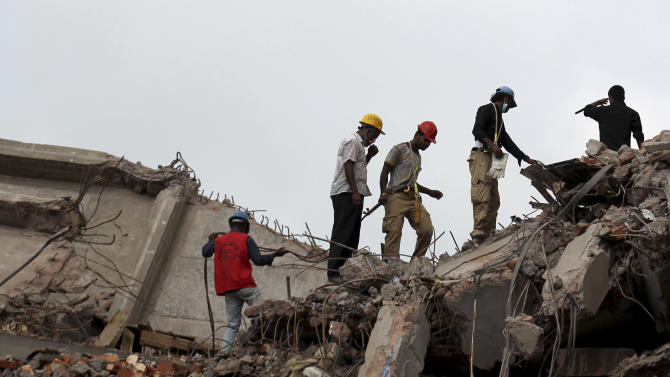 Workers and army personnel toil in the collapsed garment factory building in search for bodies on Thursday, May 2, 2013. Rescuers found more bodies in the concrete debris of a collapsed garment factory building Thursday and authorities say it may take another five days to clear the rubble. In addition to the 430 confirmed dead, police report another 149 people are still missing in what has become the worst disaster for Bangladesh's $20 billion-a-year garment industry that supplies global retailers. (AP Photo/Wong Maye-E)