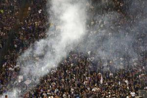 Supporters are seen behind smoke from flares before the Italian Cup final soccer match between Fiorentina and Napoli at the Olympic stadium in Rome