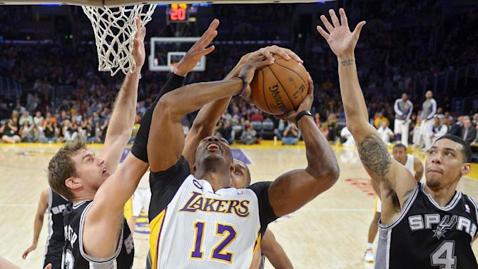 Los Angeles Lakers center Dwight Howard (12) has his shot blocked by San Antonio Spurs forward Tim Duncan, obscured, as center Tiago Splitter, left, of Brazil, and guard Danny Green defend during the first half of their NBA basketball game, Sunday, April 14, 2013, in Los Angeles. (AP Photo/Mark J. Terrill)
