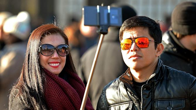 """FILE - In this Jan. 23, 2015 file photo, tourists use a 'selfie stick' in London. You can bring your beach towels and floral headbands, but forget that selfie stick if you're going to the Coachella or Lollapalooza music festivals. The sticks are banned this year at the events in Indio, Calif., and Chicago. Coachella dismissed them as """"narsisstics"""" on a list of prohibited items. Selfie sticks have become a popular but polemical photo-taking tool: Avid picture takers like perching their cellphones on the lengthening devices to snap their own shots in front of monuments and sunsets, but critics dismiss them as obnoxious and potentially dangerous to others. Museums in the U.S. and Europe, including the Palace of Versailles outside Paris and Britain's National Gallery in London, have banned them. (AP Photo/PA, John Stillwell) UNITED KINGDOM OUT"""