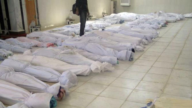 "This citizen journalism image provided by Shaam News Network taken Saturday, May 26, 2012, purports to show shrouded dead bodies following a Syrian government assault on Houla, Syria. The Syrian government denied Sunday its troops were behind an attack on a string of villages that left more than 90 people dead, blaming the killings on ""hundreds of heavily-armed gunmen"" who also attacked soldiers in the area. Friday's assault on Houla, an area northwest of the central city of Homs, was one of the bloodiest single events in Syria's 15-month-old uprising. The U.N. says 32 children under 10 were among the dead. (AP Photo) THE ASSOCIATED PRESS IS UNABLE TO INDEPENDENTLY VERIFY THE AUTHENTICITY, CONTENT, LOCATION OR DATE OF THIS CITIZEN JOURNALISM IMAGE"