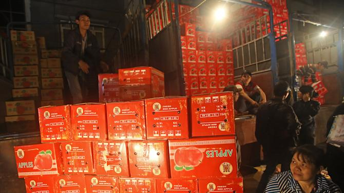 In this March 9, 2013 photo,  a porter, top, unloads boxes of Chinese red apples at Long Bien wholesale market for fruits and vegetables in Hanoi, Vietnam.  China has emerged as one of the world's leading exporters of fruit and vegetables, and is increasingly taking market share from U.S. producers in Asian markets. It grows more apples than any other country. There are no figures on how much of the crop Vietnam imports. Chinese fruit is often cheaper than Vietnamese, and offers more variety. (AP Photo/Na Son Nguyen)