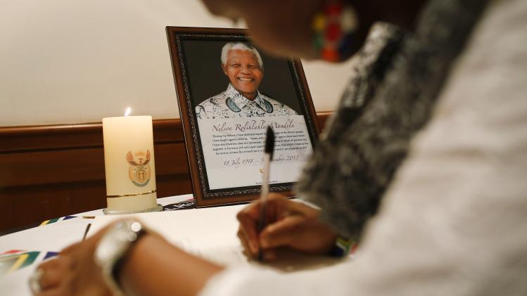 A woman writes her condolence message in a book for late former South African President Mandela at a memorial service in Mumbai