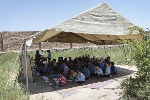In this Thursday, July 5, 2012 photo, Afghan students pass their mid- year school examinations under a tent at the Mirbachakot high school on the outskirts of Kabul, Afghanistan. Afghanistan will seek at least $4 billion from international donors this weekend at a crucial aid conference aimed at propping up the country after most foreign combat troops leave at the end of 2014. (AP Photo/Musadeq Sadeq)