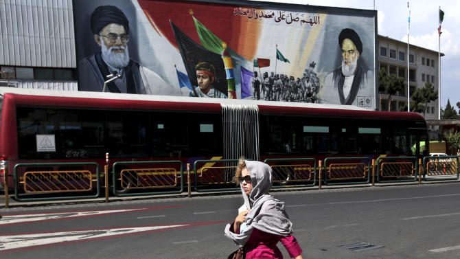 In this Thursday, May 23, 2013 photo, an Iranian woman, makes her way, at the Enqelab-e-Eslami (Islamic Revolution) street, in front of a mural of the Iranian late revolutionary founder Ayatollah Khomeini, right, a member of Basij paramilitary force, center, and supreme leader Ayatollah Ali Khamenei, in Tehran, Iran.  On the roughneck streets in south Tehran, paramilitary volunteers look to the most hard-line presidential candidate as the best defender of the Islamic system. On the other end of Tehran's social ladder, a university professor plans to snub next week's election. In between is a mix of splintered views, apathy and indecision based on dozens of AP interviews suggesting a still wide open race. (AP Photo/Vahid Salemi)