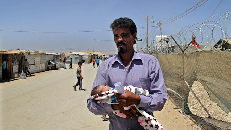 """In this Wednesday, July 24, 2013 photo, Syrian refugee Ali Shteiwi holds his newborn daughter, Taymaa, at the Zaatari refugee camp in Mafraq, Jordan, near the border with Syria. Shteiwi and his pregnant wife, Walaa, fled war and destruction in their native Syria six months earlier to find themselves trapped with tens of thousands of other refuges in the fenced desert camp in neighboring Jordan. On Monday, when Britain's future king was born, Walaa, 20, gave birth to a baby girl the couple named Taymaa - Arabic for a huge arid desert. """"This ugly desert was the only thing I could think of when I named my daughter so it would remain a stark reminder of the dark times we're living,"""" said Ali, 39. (AP Photo/Raad Adayleh)"""