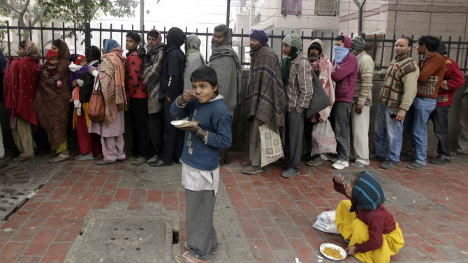 Impoverished and homeless people stand in a queue to receive free food from a volunteer organization in front of a temple, in New Delhi, India, Tuesday, Jan. 1, 2013. India will send billions of dollars in social welfare money directly to its poor under a new program inaugurated Tuesday, aiming to cut out the middlemen blamed for the massive fraud that plagues the system.  (AP Photo/Manish Swarup)