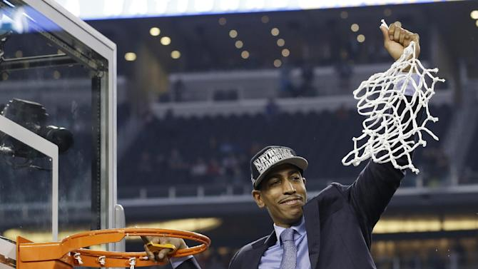 Connecticut head coach Kevin Ollie cuts down the net after his team's 60-54 victory over Kentucky in the NCAA Final Four tournament college basketball championship game Monday, April 7, 2014, in Arlington, Texas