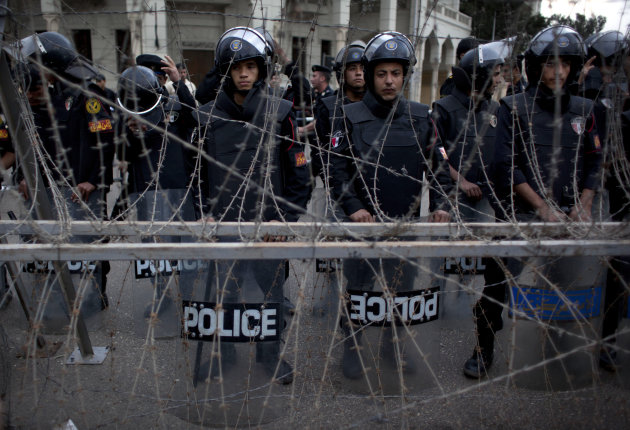 Egyptian riot police stand guard behind barbed wire while protesters chant anti Muslim Brotherhood slogans, not pictured, during a demonstration in front of the presidential palace, in Cairo, Egypt, T