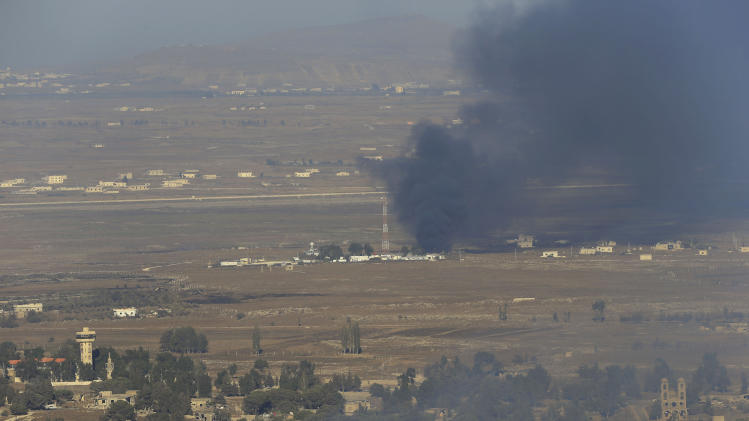 Smoke rises near a U.N. post in the Quneitra province as Syrian rebels clash with President Bashar Assad's forces, as seen from the Israeli-controlled Golan Heights, Wednesday, Aug. 27, 2014. Syrian rebels, including fighters from an al-Qaida-linked group, seized control of a frontier crossing with Israel in the Golan Heights on Wednesday after heavy clashes with Assad's forces, activists and rebels said. (AP Photo/Ariel Schalit)