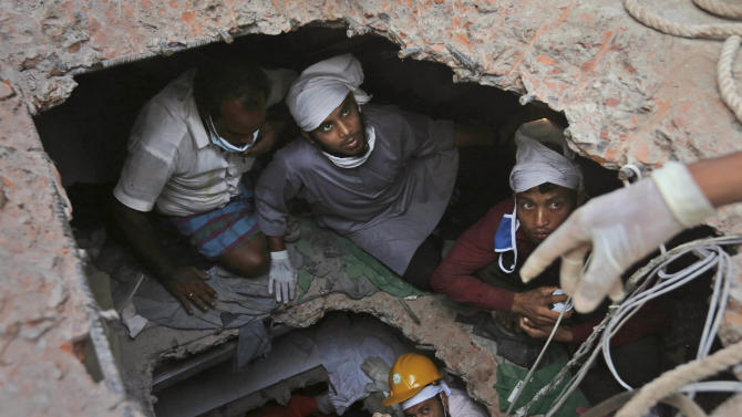 FILE - In this April 28, 2013 file photo, Bangladeshi rescue workers search for survivors as they are seen through a hole in the roof a building that collapsed Wednesday in Savar, near Dhaka, Bangladesh. Hundreds of volunteers rushed to the site of a building that collapsed last week to rescue thousands of people trapped in the rubble. They were ordinary folk - self-taught medics and neophyte rescuers.  (AP Photo/Kevin Frayer File)