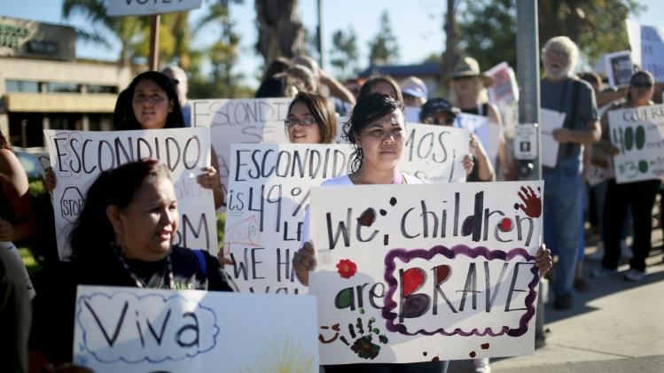 Pro-Immigration protesters hold posters as they march towards Escondido City Hall