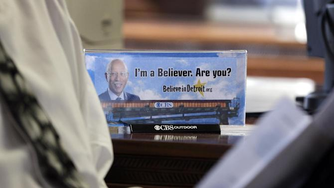 FILE - In this March 6, 2013 file photo a photograph of a billboard sits on Detroit Mayor Dave Bing's desk during his interview with the Associated Press in Detroit. The former NBA great, who transitioned smoothly to owner and founder of a steel supply company, became Mayor of Detroit in 2009.  In basketball and business, he never side-stepped a challenge, but the overwhelming weight of Detroit's financial problems and other troubles have convinced Bing to pass control of the city over to the state.  (AP Photo/Carlos Osorio, File)