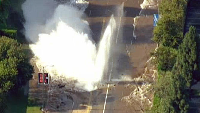water rushes into the air after a water main burst on Sunset Boulevard
