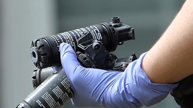 A Gwinnett County Police Department crime scene investigator carries a handful of used stun grenades Thursday afternoon, April 11, 2013, outside the Suwanee, Ga., house where Lauren Brown held firefighters hostage the night before. (AP Photo/Atlanta Journal Constitution, Ben Gray) GWINNETT OUT  MARIETTA OUT