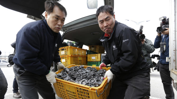 A South Korean worker, left, who arrives with products from North Korea's Kaesong is helped by a South Korean man who greeted him at the customs, immigration and quarantine office near the border village of Panmunjom, that has separated the two Koreas since the Korean War, in Paju, north of Seoul, South Korea, Thursday, April 11, 2013. As the world braced for a provocative missile launch by North Korea, with newscasts worldwide playing up tensions on the Korean Peninsula, the center of the storm was strangely calm. (AP Photo/Lee Jin-man)