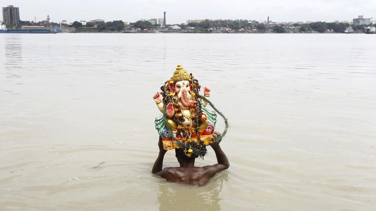 A devotee immerses an idol of the Hindu elephant god Ganesh in the waters of river Ganga during the ten-day-long Ganesh Chaturthi festival in Kolkata