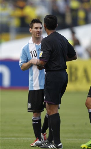 Argentina's Lionel Messi, talks to Paraguay's referee Enrique Caceres during a 2014 World Cup qualifying soccer game against Ecuador in Quito, Ecuador, Tuesday, June 11, 2013