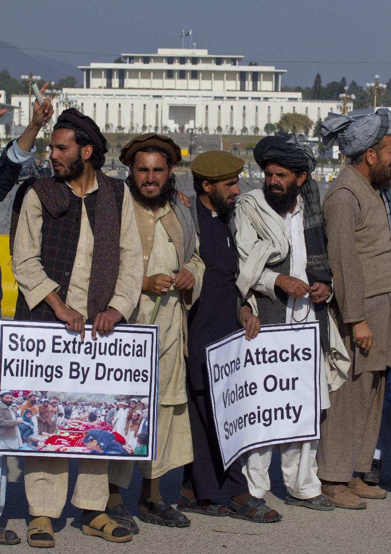 Pakistani tribal villagers affected by U.S. drone attacks participate in a rally near President house, seen top back, in Islamabad, Pakistan on Saturday, Feb, 25, 2012. Dozens of tribal villagers form Waziristan region rallied in the capital Islamabad against drone attacks in Pakistani tribal areas. (AP Photo/Anjum Naveed)