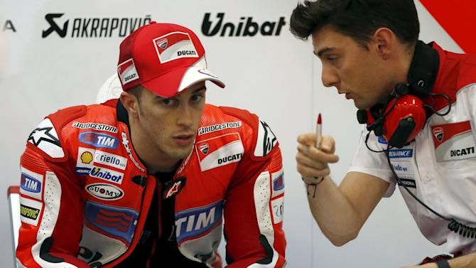 Ducati MotoGP rider Andrea Dovizioso of Italy talks with his team member in his garage during qualifying session for Sunday's Japanese Grand Prix at the Twin Ring Motegi circuit