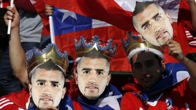 Chilean fans hold masks of Chile's Arturo Vidal before their Copa America 2015 final soccer match against Argentina at the National Stadium in Santiago