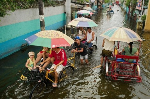 <p>People use pedicabs to cross floodwaters in a street in Valenzuela, on the outskirts of Manila, on August 13. The authorities rushed relief supplies to the country's remote north on Tuesday in preparation for a new storm, which was also expected to dump heavy rain on other areas struggling with deadly floods.</p>