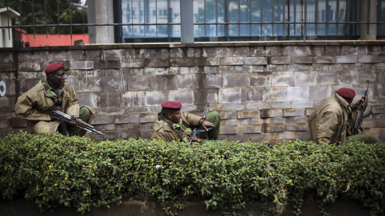 "Kenya security forces are seen behind a wall outside the Westgate Mall in Nairobi, Kenya Monday morning, Sept. 23, 2013. Kenya's military launched a major operation at the upscale Nairobi mall and said it had rescued ""most"" of the hostages being held captive by al-Qaida-linked militants during the standoff that killed at least 68 people and injured 175. (AP Photo/Jerome Delay)"