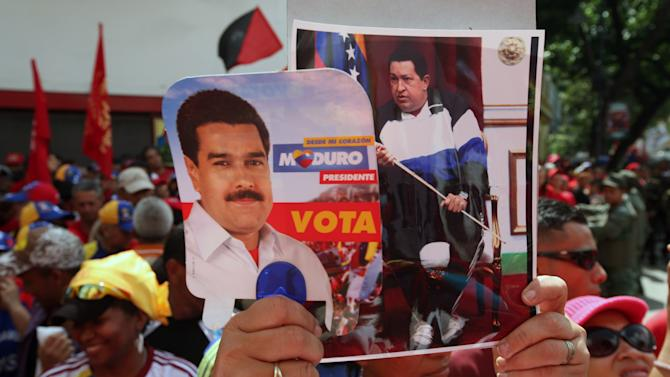 A woman holds up images of President-elect Nicolas Maduro and the late Hugo Chavez as supporters gather outside the Parliament building where Maduro's inaugural ceremony takes places, in Caracas, Venezuela, Friday, April 19, 2013. The opposition boycotted the ceremony, hoping that the ruling party's last-minute decision to allow an audit of nearly half the vote could change the result in a the bitterly disputed presidential election. (AP Photo/Gil Montano)