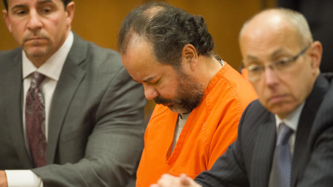 Ariel Castro, center, sits before a judge with his defense attorney's, Craig Weintraub, left, and Jaye Schlachet during a pretrial hearing on Wednesday, June 19, 2013, in Cleveland.. A tentative Aug. 4 trial date has been set for Castro, accused of kidnapping three women and holding them in his home for about a decade.  (AP Photo/Jason Miller)