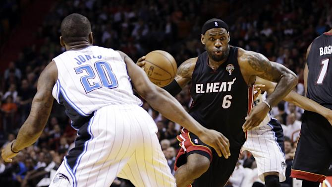 Miami Heat's LeBron James (6) drives around Orlando Magic's DeQuan Jones (20) during the first half of an NBA basketball game in Miami, Wednesday, March 6, 2013. (AP Photo/J Pat Carter)