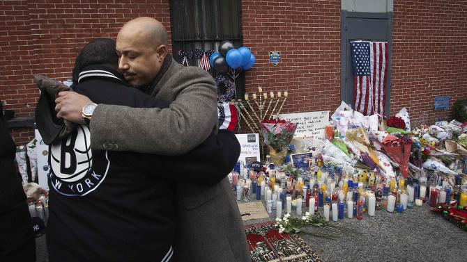 President of Brooklyn Chapter of the National Action Network Kirsten John Foy hugs a supporter at a makeshift memorial at the site where two police officers were fatally shot in Brooklyn