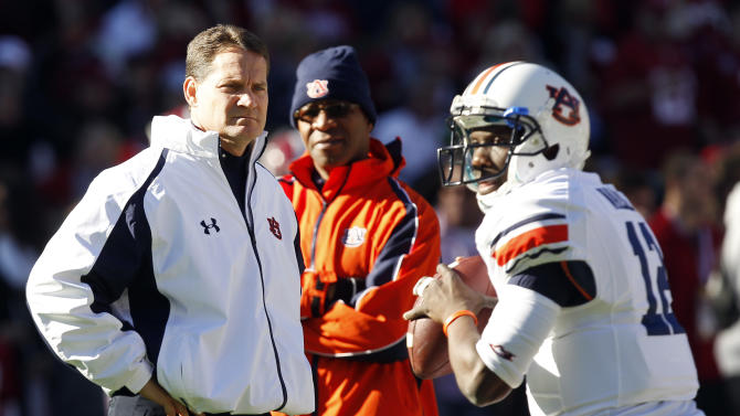 Auburn coach Gene Chizik, left, watches as  quarterback Jonathan Wallace (12) warms up before the first half of an NCAA college football game against Alabama on Saturday, Nov. 24, 2012, in Tuscaloosa, Ala. (AP Photo/Butch Dill)