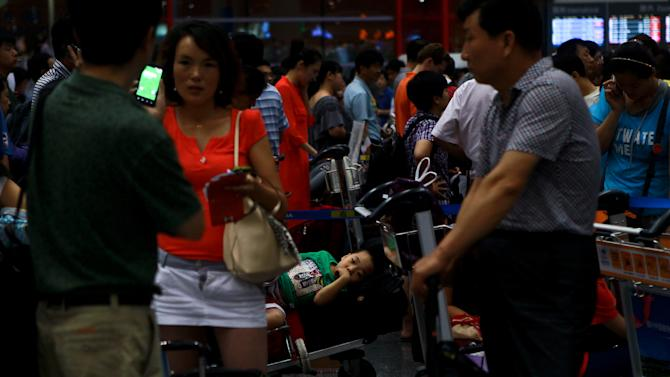 Passengers stranded at the Beijing Capital International Airport after flights are canceled due to the heavy rains in Beijing, China, Saturday, July 21, 2012. Heavy downpour flooded roads and caused hundreds of flights to be canceled in the capital. (AP Photo) CHINA OUT