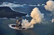 A Japan Coast Guard handout photo taken on November 20, 2013 shows smoke rising from a new islet created by a volcanic eruption in southern Japan
