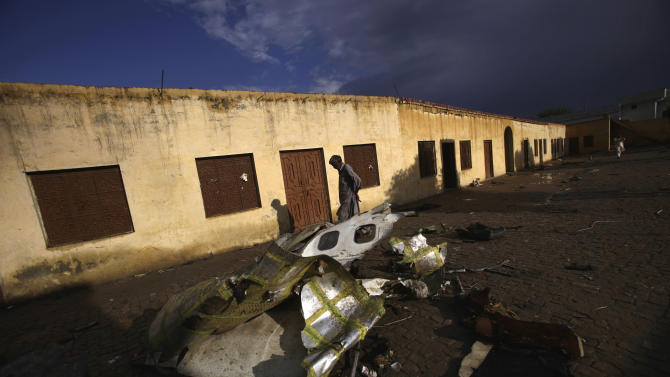 A Pakistani man walks by the wreckage of a Bhoja Air Boeing 737 passenger plane that crashed on Friday, killing all 127 people on board, on the outskirts of Islamabad, Pakistan, Sunday, April 22, 2012. Pakistan barred the head of the airline whose jet crashed near the capital from leaving the country, vowing to investigate the tragedy that revived fears about the safety of aviation in the country saddled by massive economic problems. (AP Photo/Muhammed Muheisen)