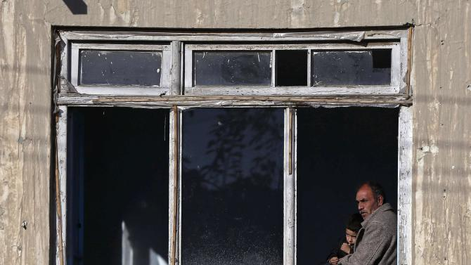 An Afghan man, with a child, watches from his home window near the site where a bus was hit by a remote-controlled bomb in Kabul