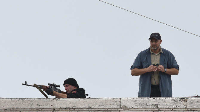An Albanian special forces member looks through the scope of his rifle as he stands on a roof top in Mother Teresa Square before the arrival of Pope Francis, in Tirana, Sunday, Sept. 21, 2014. Security was unusually tight for Francis' visit to the majority Muslim country amid reports that militants who trained in Iraq and Syria had returned and might pose a threat. The Vatican insisted no special security measures were taken, but Francis' interactions with the crowd were very different than from his previous foreign trips: His open-topped vehicle sped down Tirana's main boulevard, not stopping once for Francis to greet the faithful as is his norm. (AP Photo/Hector Pustina)